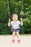 Happy smiling little boy toddler in tshirt and jeans shorts on swing on backyard playground outside Royalty Free Stock Photography