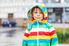 Happy smiling little boy walking in city through rain Royalty Free Stock Images