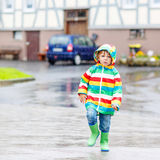 Happy smiling little boy walking in city through rain Royalty Free Stock Photo