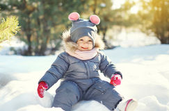 Happy smiling little child playing on snow in winter Royalty Free Stock Images