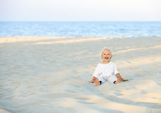 Happy smiling little child sitting on the sunny beach. Royalty Free Stock Photography