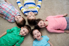 Happy smiling little children lying on floor Royalty Free Stock Images