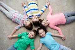 Happy smiling little children lying on floor Stock Images