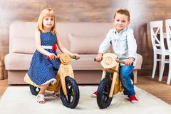 Happy little children riding a runbikes at home stock image