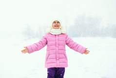 Happy smiling little girl child enjoys snowflakes in winter Stock Image