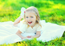 Happy smiling little girl child lying on grass in sunny summer. Day Stock Images