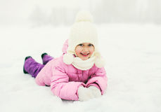Happy smiling little girl child lying on snow in winter Stock Photos