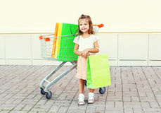Happy smiling little girl child and trolley cart with shopping bags in city Royalty Free Stock Photography