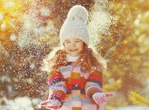Happy smiling little girl child in winter over a snowy background. Happy smiling little girl child in winter over snowy background