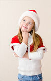 Happy smiling little girl in christmas hat is dreaming Royalty Free Stock Image