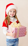 Happy smiling little girl with christmas present Stock Photos
