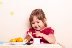 Happy smiling little girl eating fruits and yogurt Stock Photography