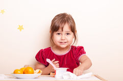Happy smiling little girl eating fruits and yogurt Royalty Free Stock Photography