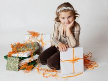 Happy smiling little girl between gifts royalty free stock photo