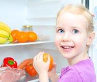 Happy smiling little girl holding orange Stock Images