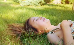 Happy smiling little girl lying on the grass in sunny summer day Royalty Free Stock Photography