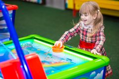 Happy smiling little girl play air hockey stock image
