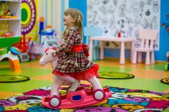Happy smiling little girl riding a wooden horse swing Stock Photo