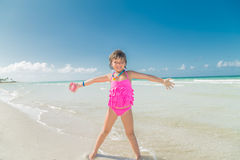 Happy smiling little girl standing on the beach and enjoying her vacation, leisure time Royalty Free Stock Image
