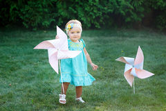 Happy smiling little girl standing on meadow and holding toy white pinwheel windmill Stock Photos
