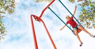 Happy smiling little girl swing on the swing stock images