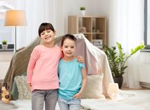 Happy smiling little girls hugging at home. Childhood, friendship and people concept - happy smiling little girls hugging at home over kids room and tepee Royalty Free Stock Photos