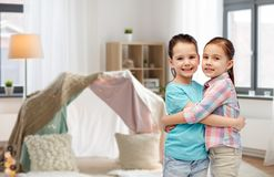 Happy smiling little girls hugging at home. Childhood, friendship and people concept - happy smiling little girls hugging at home over kids room and tepee Stock Photography