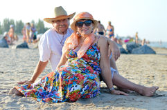 Happy smiling & looking at camera mature couple sitting at seashore on sandy beach Royalty Free Stock Image
