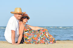 Happy smiling & looking at camera mature couple sitting at seashore on sandy beach Royalty Free Stock Images