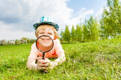 Happy smiling through magnifier boy lays on grass Stock Photos