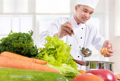 Male chef put some ingredient in the pot. Happy smiling male chef cooking put some ingredient in the pot Royalty Free Stock Photography