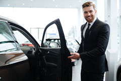 Happy smiling male dealer inviting customers. To sit in a new car Royalty Free Stock Photos