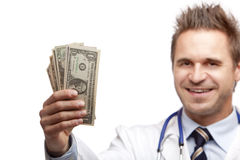 Happy smiling male doctor with us dollar bills Royalty Free Stock Image