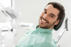 Happy smiling male patient at dental clinic. Medicine, dentistry and healthcare concept - happy smiling male patient on chair at dental clinic Royalty Free Stock Image