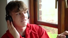 Male teenager young man teen sitting by a window listening to music on wireless blue tooth headphones. Happy smiling male teenager young man teen wearing a red stock video footage