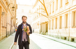 Happy smiling man with baguette and flower bouquet walking down the street Royalty Free Stock Photography