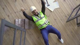 Happy smiling man in builder`s helmet and green jacket lying on the floor showing victory gestures and looking up. Profession concept. The guy resting after stock video footage