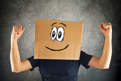 Happy smiling man with cardboard box on his head and raised fist Royalty Free Stock Photos