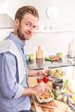 Happy smiling man or chef preparing dinner Stock Image