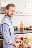 Happy smiling man chopping vegetables to make salad Stock Images