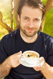 Happy smiling man drinking coffee in the garden Stock Photos