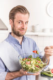 Happy smiling man eating fresh vegetable salad in the kitchen Stock Photography