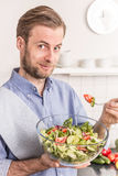 Happy smiling man eating fresh vegetable salad in the kitchen Royalty Free Stock Images