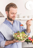 Happy smiling man eating fresh vegetable salad in the kitchen Royalty Free Stock Photography