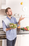 Happy smiling man with a fresh vegetable salad in the kitchen Stock Photography