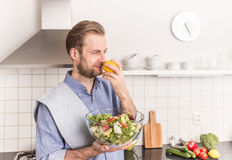 Happy smiling man with a fresh vegetable salad in the kitchen Stock Photos