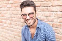 Happy smiling  man with glasses leaning against brick wall Stock Images