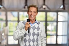 Happy smiling man holding microphone. Cheerful middle-aged man with microphone on abstract window background. Television presenter at tv programm stock photos
