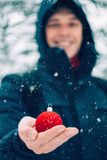 Happy man holding red Christmas ball in his hand in front of snow covered fir Christmas tree, outdoors. Selective focus. Happy smiling man holding red Christmas royalty free stock photos