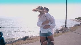 Happy smiling man hugs and kisses girlfriend slow motion. Happy smiling man hugs and kisses girlfriend against ocean waves reflecting sunlight slow motion stock video footage